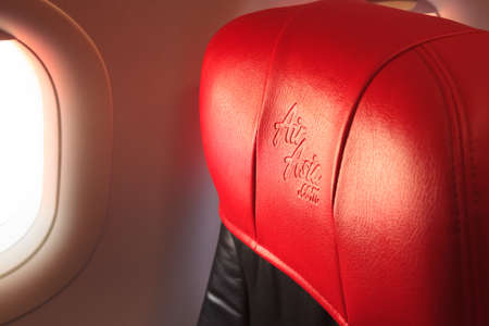 Bangkok, Thailand - June 10, 2019: Air Asia Airline Logo imprinted on the red leather seat headrest is seen from passenger window view background. Business, Transportation and Travel concept