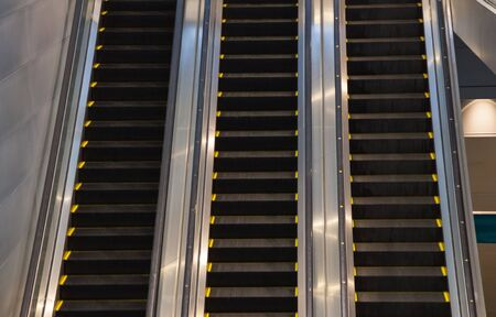 Escalators in subway train station towards upper levels, used in places where lifts would be impractical. Transportation between floors or levels in subways, buildings, and other mass pedestrian areas