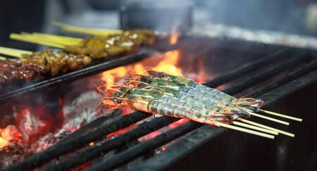 Grilled Prawns is marinated prawn skewer stick barbecued on charcoal fire grill. Asian Food Travel, Singaporean Traditional Street Food, Fast Food, Culinary, Cuisine, Appetizer and Gourmet concept