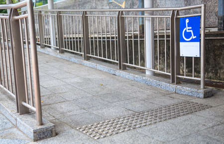 Access Ramp Sign for wheelchair ramp, an inclined plane installed in addition to or instead of stairs, for wheelchair users, people pushing strollers, carts, or wheeled objects to access buildings. Foto de archivo