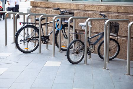 Bicycle top tubes are securely chained, by chain links and locks, to the metal bike racks. Outdoor Activity, Exercise, Sport, Environmentally Friendly Transportation and City Bike Security concept