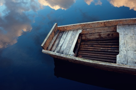 Wooden boat in the clouds reflected in water