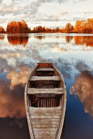 the boat on the river: Barco de madera en el lago con el reflejo de las nubes