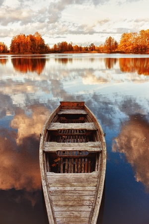 row boat: Wooden boat in the lake with the reflection of clouds Stock Photo