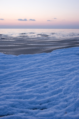 The frozen snow on the sea at sunset photo