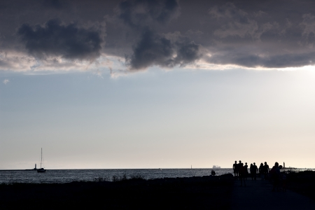 People walking on the sea at the mouth of the river