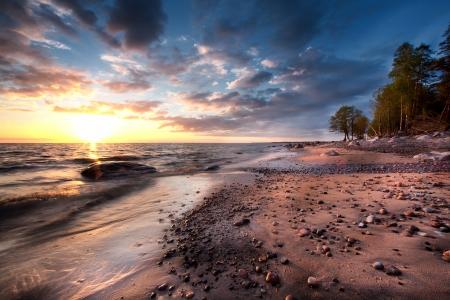 outcast: Sandy beach with rocks at the sea Stock Photo