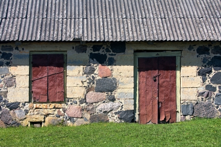 The wall with the window and the door of the old stone house