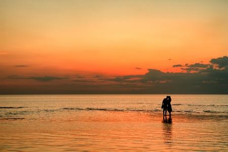 Couple on the beach at sunset photo