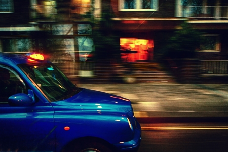 Taxis in London at a speed over the houses Stock Photo
