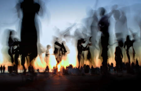 People dancing on the beach against the setting sun photo