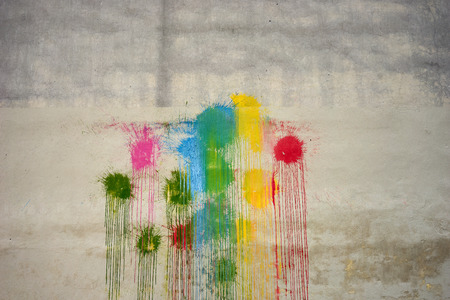 Colors of the rainbow paint stains on the wall