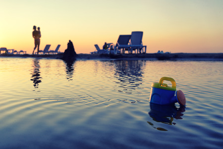jurmala: A woman with a baby and a toy watering can on the beach at sunset in Jurmala