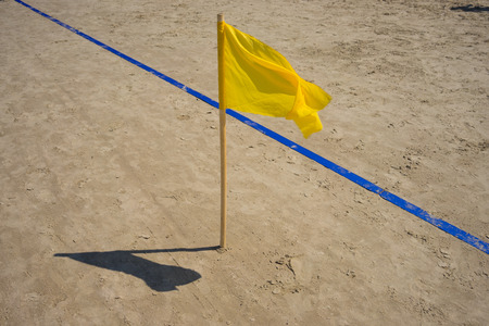 Yellow flag and the blue line on the golden sand beach