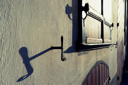 Window with shutters on a white wall with shadows. Vecriga, Riga, Latvia photo