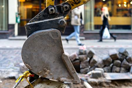 Excavator bucket on a background of street repairs. Riga, Latvia