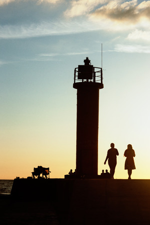 baltic people: People came to the lighthouse to see off the day at sunset, Latvia. Baltic sea Stock Photo