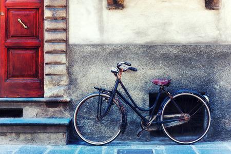 Vintage fiets tegen de muur tegenover de deur naar het huis. Italië. Toscana