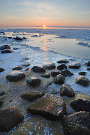 froze: Stones in the sea froze in the ice at sunset. Baltic sea