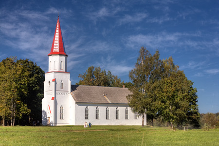 Parishioners and white church on a summer day. Latvia photo