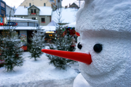 Snowman with a red nose in the city on the background of homes before Christmas and New Year in Riga