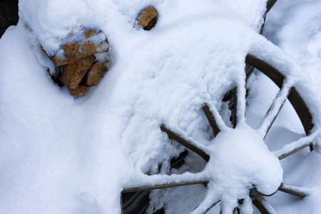 Firewood for the stove and wagon wheel under the fresh snow. Latvia, Europe