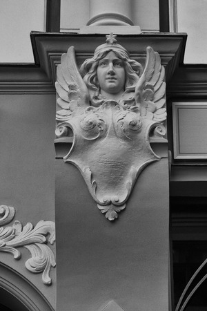 latvia girls: Bas-relief of a woman with wings and a star on the wall of an old house. Latvia