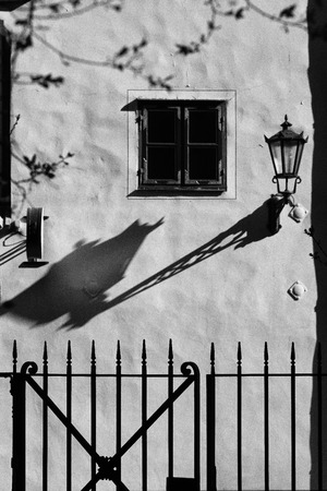 Wall of the house with a window for a stylish lace fence with long shadow lantern Stock Photo