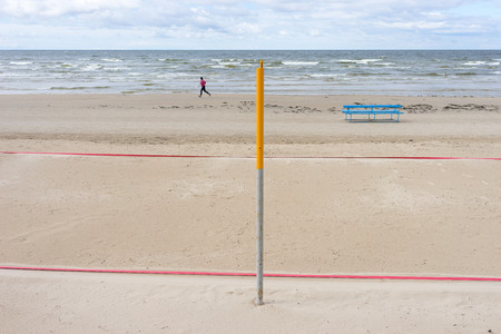 Man running along the deserted beach on the background of poles and lines