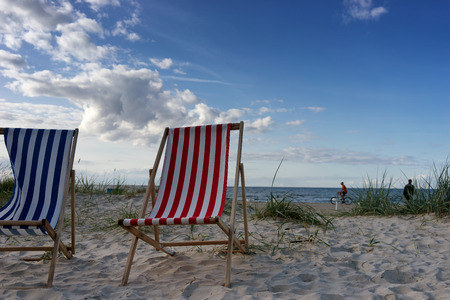 Blue and red chairs in the sand on the beach in summer and cyclist. Baltic sea