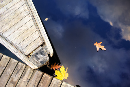 Nose of wooden boat at the dock of the boards and the leaves of autumn with reflection of blue sky