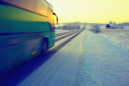 Bus rides on winter road on rural landscape in the snow towards the sun. Latvia, Europe Stock Photo
