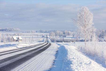 Lines asphalt winter road through rural field on the horizon. Latvia