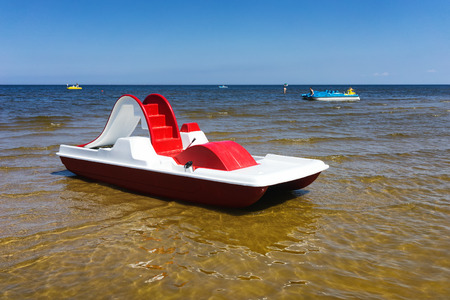 Red with a white top dinghy with pedals near the shore on the golden beach of the Baltic Sea. Jurmala. Latvia