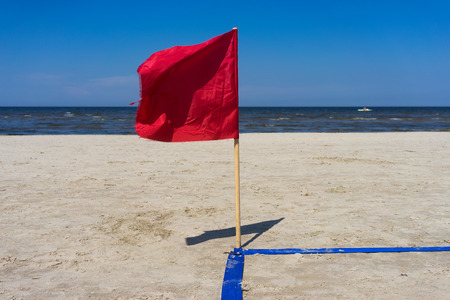 Red flag in the wind on the sandy beach with blue lines. Jurmala, Latvia