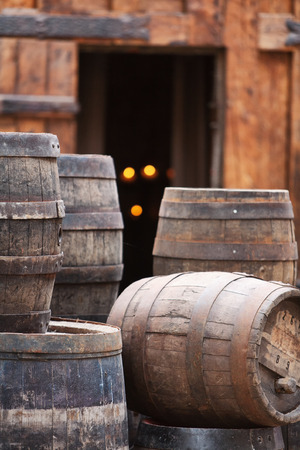 Antique oak barrels with steel hoops at the gates of the old house Stock Photo