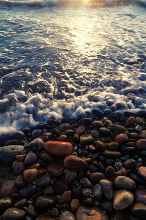 Waves on the beach of round stones during high tide at sunset