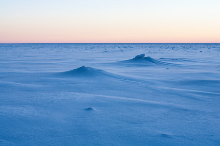Pink sky at the horizon is reflected in the frozen sea to the horizon blue velvet. Baltic sea Stock Photo