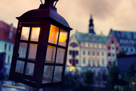 Lantern with a yellow light on the background of the evening Vecriga. Riga, Latvia