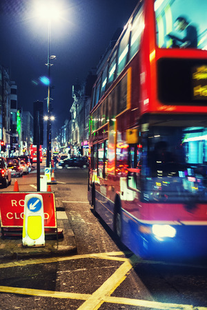 The red double-decker bus in London street lights evening Stock Photo