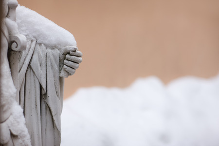 civilisation: A fragment of plaster sculpture with a hand under the snow on a background of beige wall winter