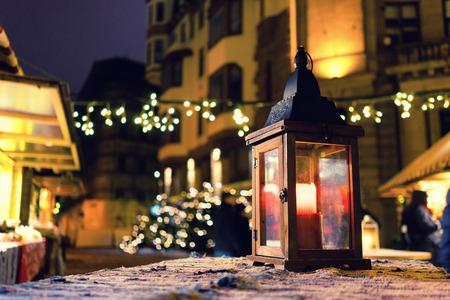 Lantern with candle lights and among the houses on Christmas Fair
