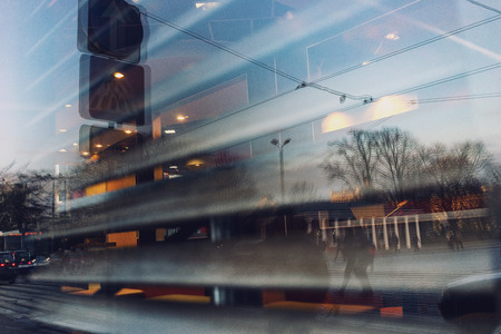 City life is reflected in the window of a cafe with linear shutters. Riga