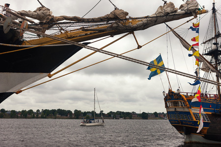 Sailboats with flags at the pier and yacht during a regatta in Riga on the Daugava