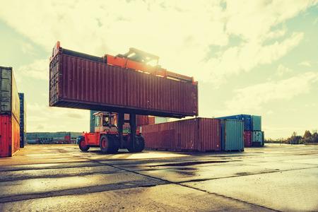 明るい晴れた日に港湾でのコンテナーの荷役 写真素材