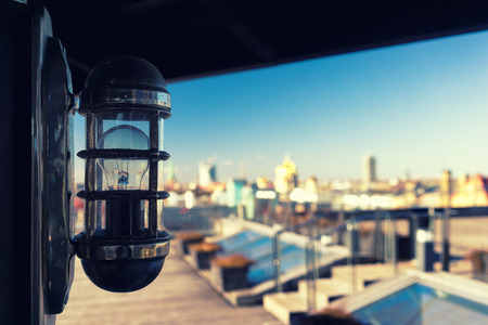Light bulb in a summer cafe on the roof over modern city background. Riga, Latvia