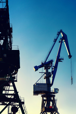 Cranes at the port for loading and unloading in the sun and sky. Riga, Latvia Stock Photo