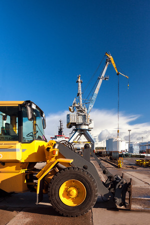 Yellow forklift and crane at unloading and loading cargo at the port on a background of blue sky Stock Photo