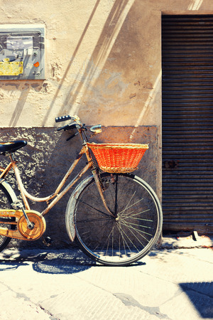 Old bicycle with a basket against the wall advertisement and the entrance to the garage in traditional Tuscany Italy Stock Photo