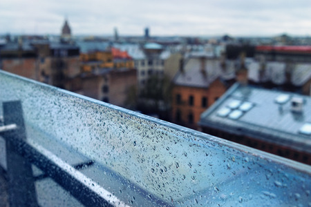 glass partition: The roofs of the city from the top of the glass partition with raindrops and the horizon Stock Photo